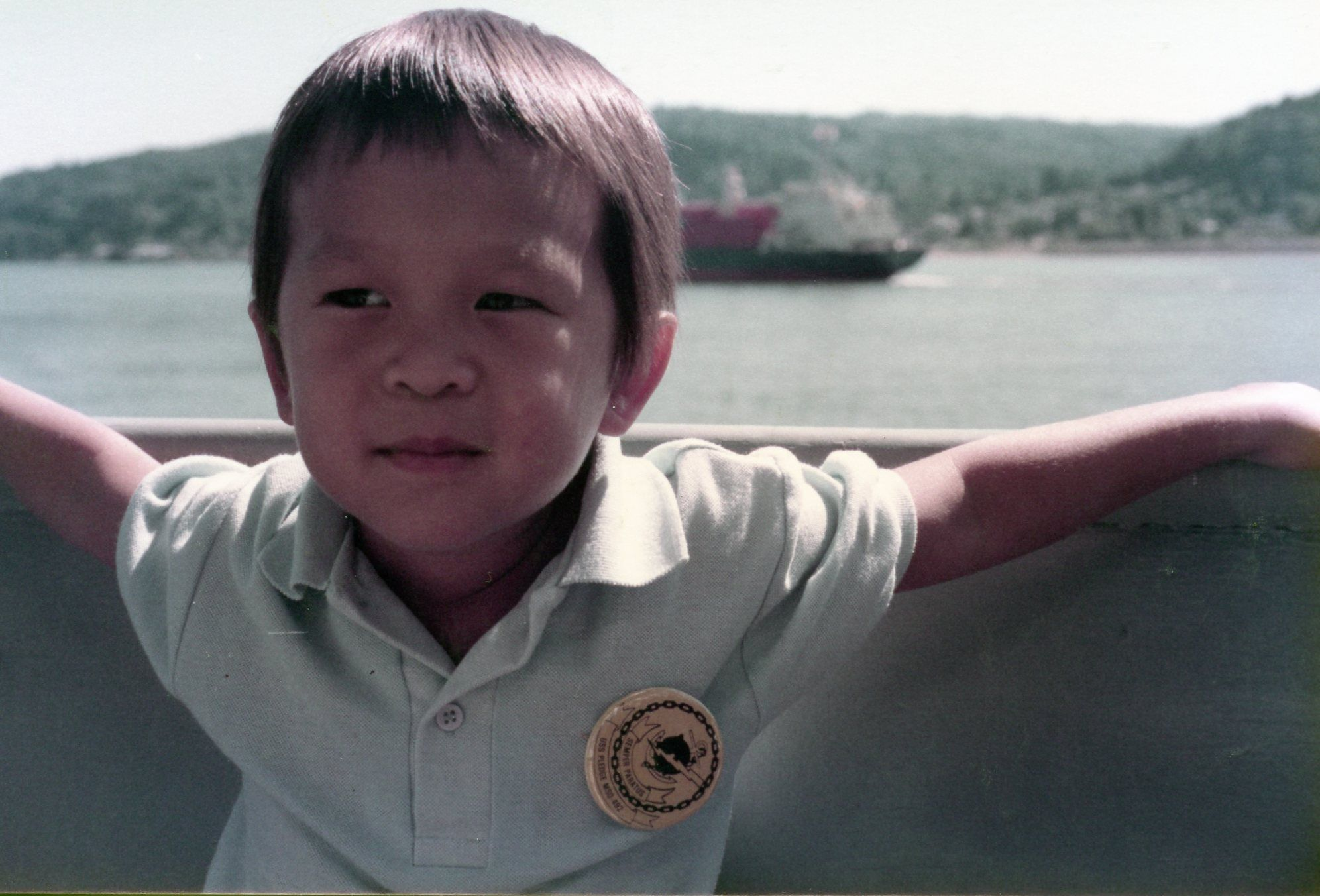 Image of Daniel Hoang as a small child sitting in a boat. In the background is a large body of water and a freight ship.
